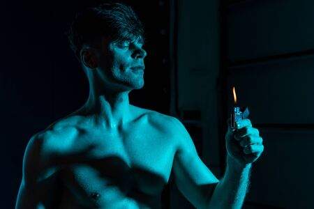sexy shirtless muscular man holding lighter in darkness Stock fotó