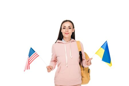 smiling student with backpack holding Ukrainian and American flags isolated on white Фото со стока