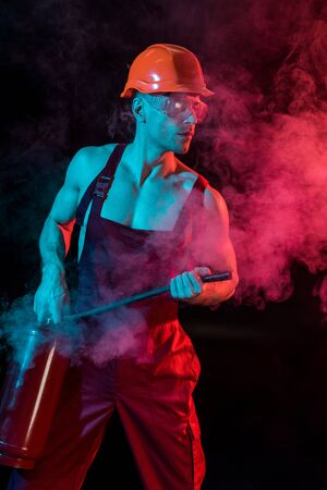 shirtless fireman in overall holding fire extinguisher in smoke on black