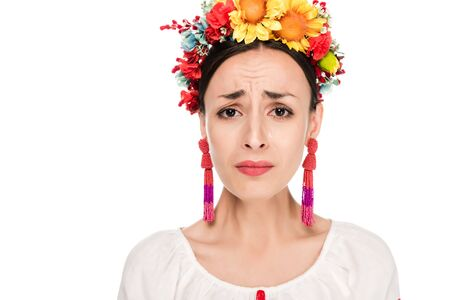 upset brunette young woman in national Ukrainian embroidered shirt and floral wreath isolated on white