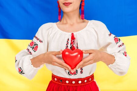 partial view of young woman in national Ukrainian costume holding red heart with flag of Ukraine on background