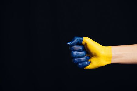 cropped view of hand painted in Ukrainian flag colors isolated on black Foto de archivo - 128146617