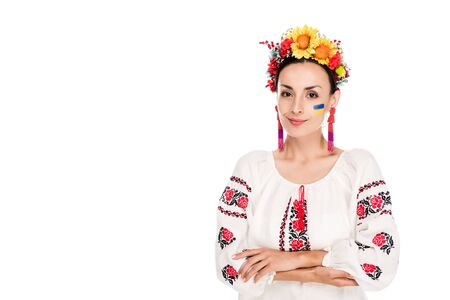 brunette young woman in national Ukrainian embroidered shirt and floral wreath with crossed arms isolated on white Banco de Imagens