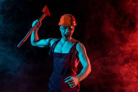 Preocupado bombero sin camisa con casco y gafas protectoras sosteniendo un hacha de cabeza plana y gritando en humo sobre negro Foto de archivo