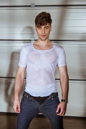 handsome man in jeans and wet white t-shirt Stock Photo