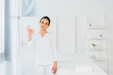 cheerful brunette woman showing ok sign in spa center Imagens
