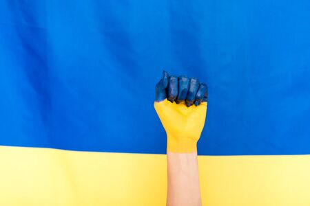 cropped view of painted hand on Ukrainian flag background Foto de archivo - 128146649
