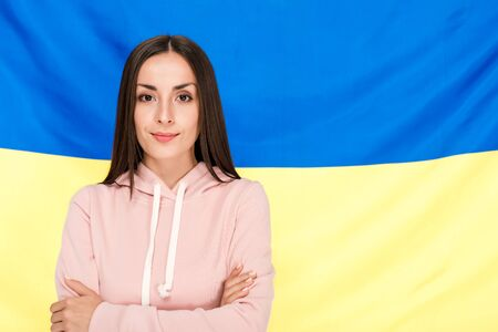 smiling brunette young woman with crossed arms standing on Ukrainian flag background Фото со стока