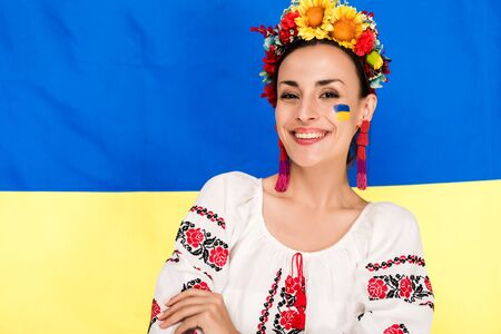 happy brunette young woman in national Ukrainian costume and floral wreath with flag of Ukraine on background