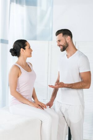 cheerful masseur gesturing while looking at attractive woman Imagens