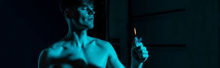 panoramic shot of sexy shirtless man holding lighter with closed eyes in darkness