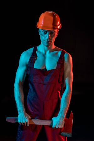 shirtless fireman in overall, hardhat and protective goggles holding flat head axe isolated on black