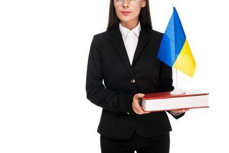 partial view of lawyer in black suit holding Ukrainian flag on book isolated on white Stock Photo