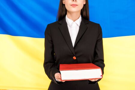 cropped view of lawyer in black suit holding book on Ukrainian flag background Banque d'images