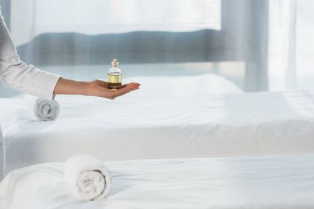 cropped view of woman holding bottle with oil near massage table in spa center Imagens