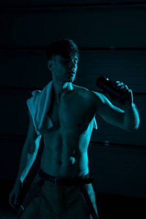 sexy shirtless man with towel holding sport bottle in darkness