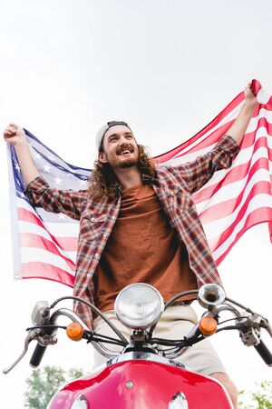 low angle view of young man standing on red scooter, smiling and holding American flag