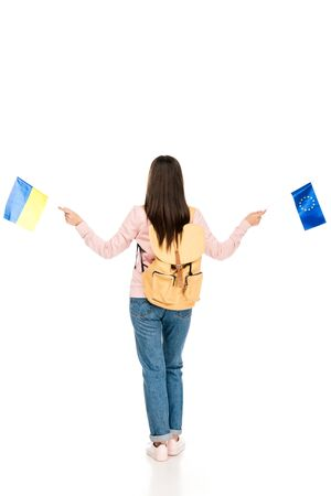 full length view of student with backpack holding Ukrainian and European flags isolated on white