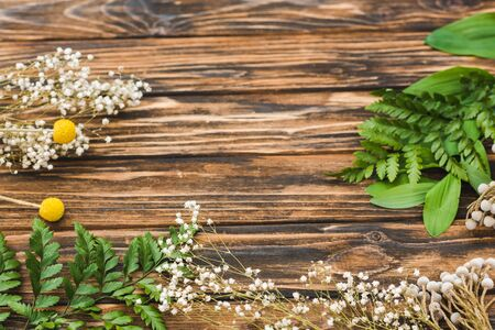 top view of white and yellow flowers and green leaves on wooden table Stock Photo