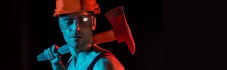 panoramic shot of shirtless fireman in hardhat and protective goggles holding flat head axe isolated on black