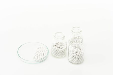 bottles with pills near glass plate isolated on white Foto de archivo - 128146775