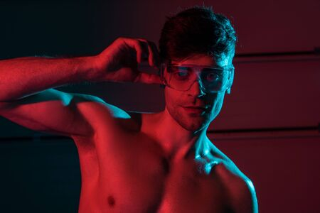 sexy shirtless fireman in protective goggles in darkness Stock Photo