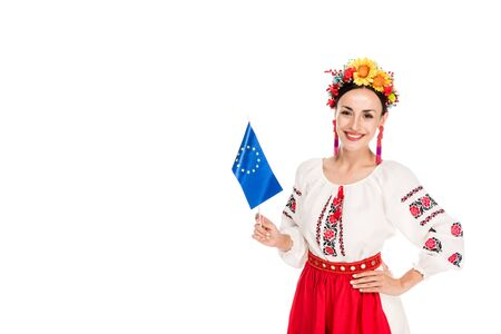 happy brunette young woman in national Ukrainian costume holding European flag isolated on white