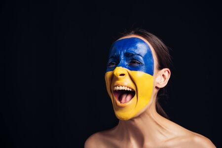 emotional young woman with painted Ukrainian flag on face screaming isolated on black