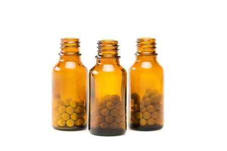 round pills in small glass orange bottles isolated on white