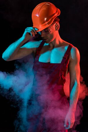 sexy shirtless fireman in overall and hardhat in smoke on black Reklamní fotografie