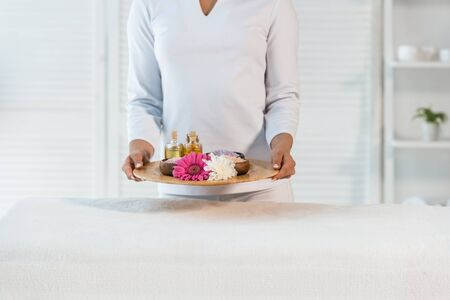 cropped view of young masseur holding tray with bottles of oil, sea salt and flowers