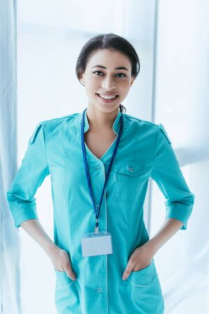 beautiful latin doctor holding hands in pockets and smiling at camera Stock Photo