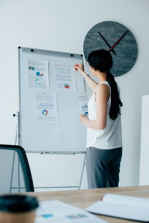 young latin businesswoman arranging infographics on flipchart in office