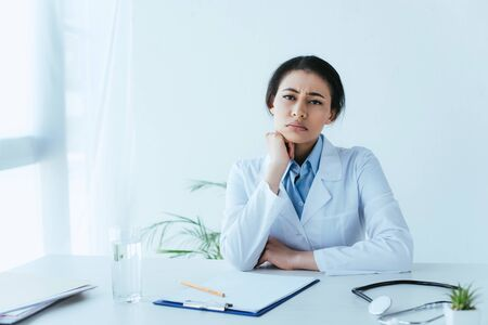 upset latin doctor looking at camera while sitting at workplace in clinic Reklamní fotografie