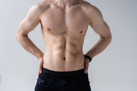 partial view of shirtless sexy man with arms akimbo isolated on grey