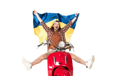 full length view of happy young man sitting on red scooter, holding Ukrainian flag in air isolated on white Stock Photo
