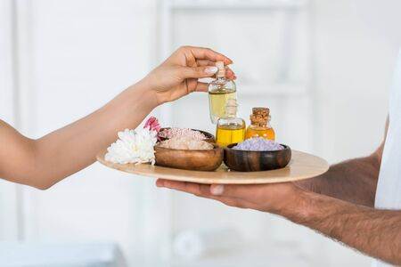 cropped view of woman taking bottle with oil while masseur holding tray