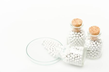 bottle with round small pills near glass petri dish isolated on white Foto de archivo - 128147037