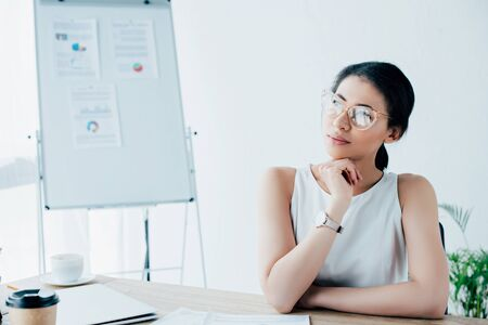dreamy latin businesswoman in glasses looking away while sitting at workplace