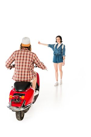 full length view of girl outstretched hand and stopping young man sitting on red scooter isolated on white
