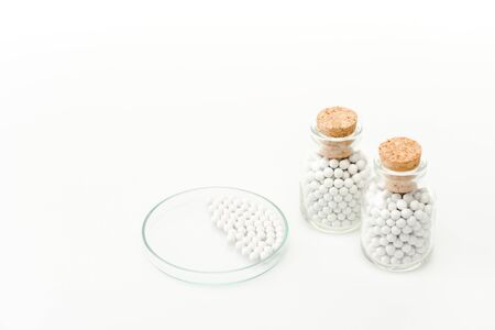 bottles with wooden corks near glass petri dish isolated on white Stock Photo
