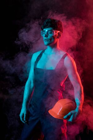 sexy shirtless fireman in overall holding hardhat in smoke on black