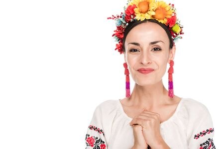 happy brunette young woman in national Ukrainian embroidered shirt and floral wreath isolated on white