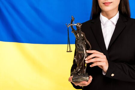 cropped view of lawyer in black suit holding Themis statuette on Ukrainian flag background