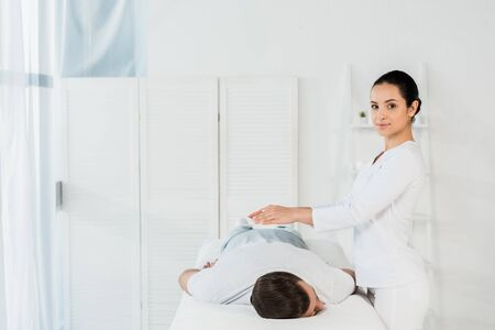 attractive healer with hands above body of man in massage table Stock Photo