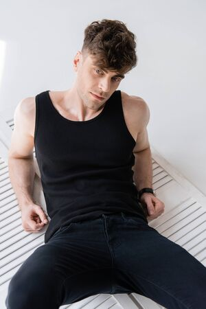 pensive handsome man in black sleeveless shirt lying on grey Banco de Imagens