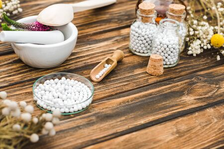 selective focus of bottles with pills near mortar with veronica flowers on wooden table Stock Photo