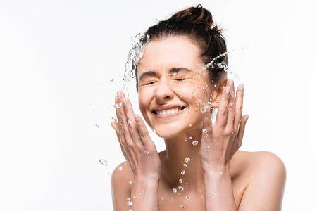 glückliche junge Frau mit natürlicher Schönheit, die mit sauberem Wasserspritzen isoliert auf weiß abspült
