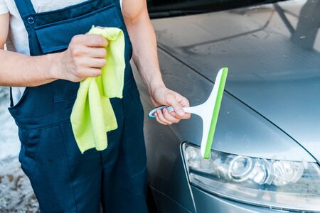 cropped view of car cleaner holding rag and squeegee near wet car Foto de archivo - 128287293