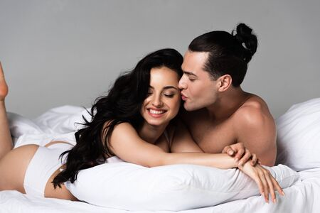 undressed couple smiling while lying on bed together